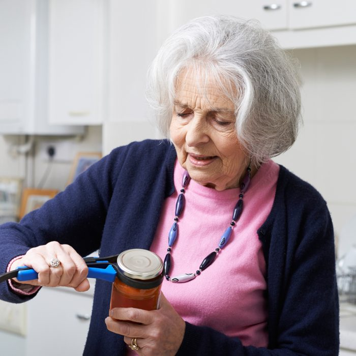 Senior Woman Taking Lid Off Jar With Kitchen Aid
