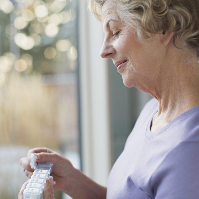 Senior woman looking down at weekly pill reminder