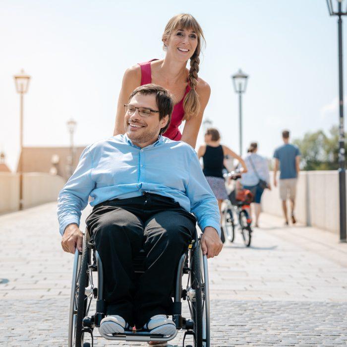 Woman and her friend in a wheelchair having stroll through the town enjoying the sun