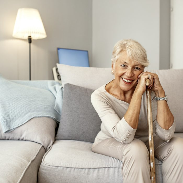 Photo of Retired short hair old woman with her walking stick at home looking at camera during the day while sitting on sofa. Senior gray hair women supporting on a walking cane at home.