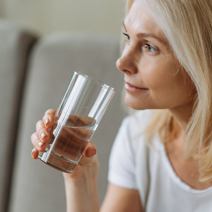 Follow healthy lifestyle. To be healthy. Mature beautiful caucasian woman holding a glass of clean water, taking care of her health, the daily norm of water