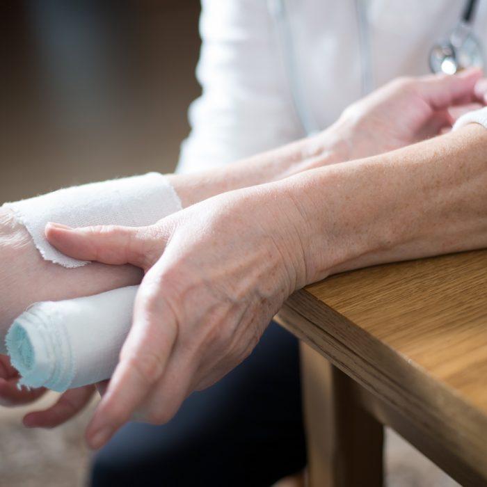 alte Frau bekommt eine Binde um den Arm gewickelt